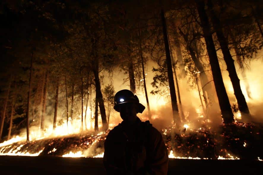 A firefighter watches for spot fires during a burnout operation while battling the Rim Fire near Yosemite National Park, Calif.