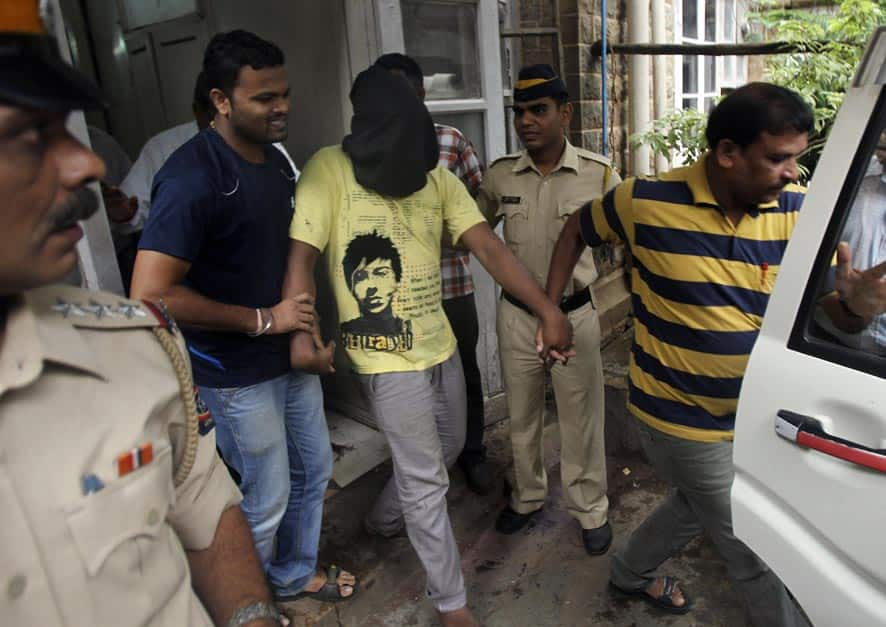 Police officials escort an accused, with the head covered with black cloth, in the gang rape of a photojournalist after producing him before a court in Mumbai.