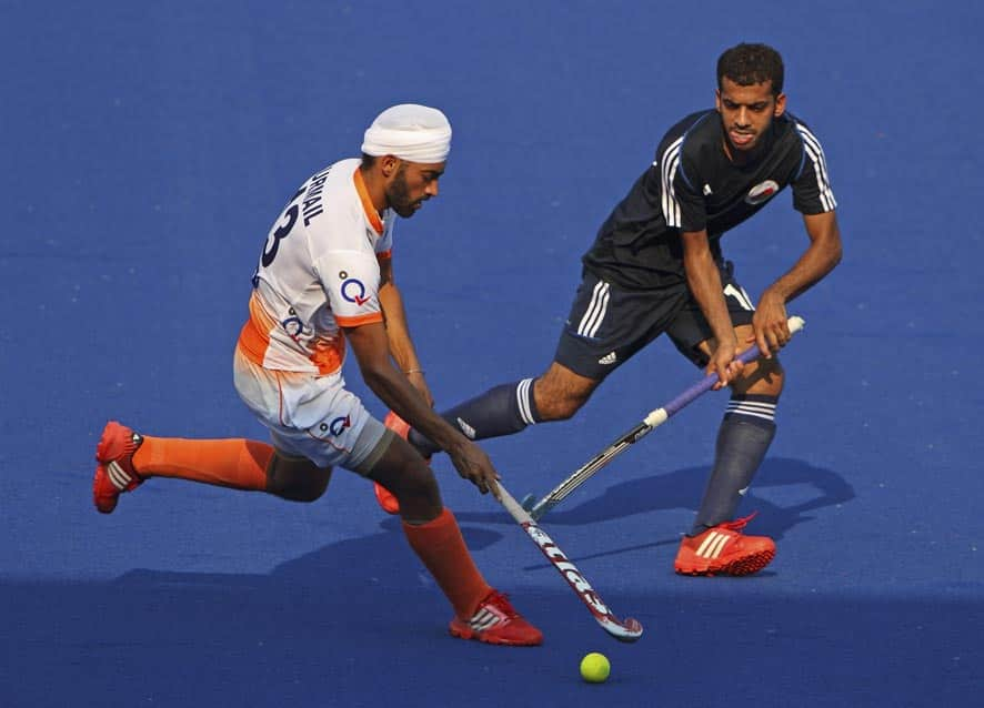 India`s Gurmail Singh, left, and Oman`s Al-Saadi Salah Nasser Ahmad battle for the ball during the 9th men`s Asia Cup field hockey tournament in Ipoh, Malaysia.