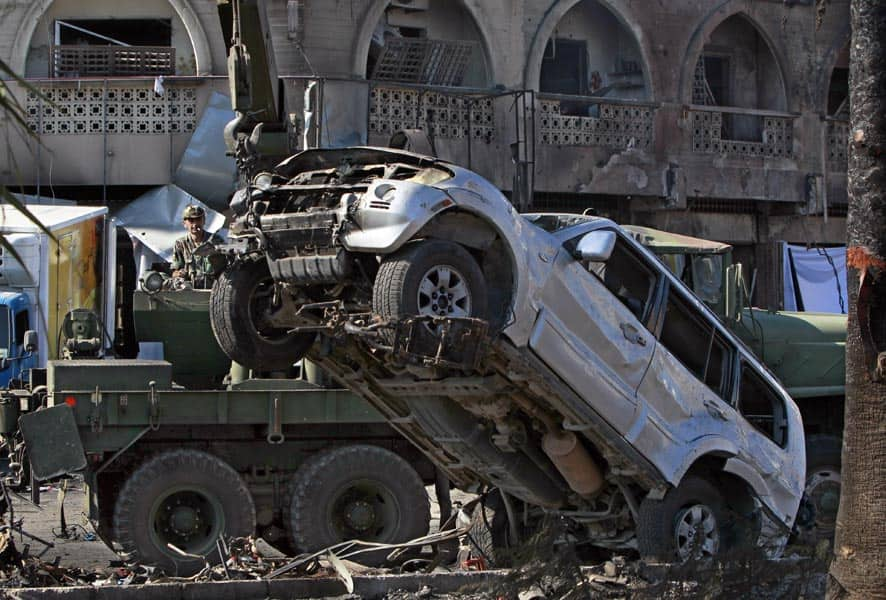 A Lebanese Army soldier moves a damaged car at the site of a car bomb explosion outside of the Al-Taqwa mosque, in the northern city of Tripoli, Lebanon.