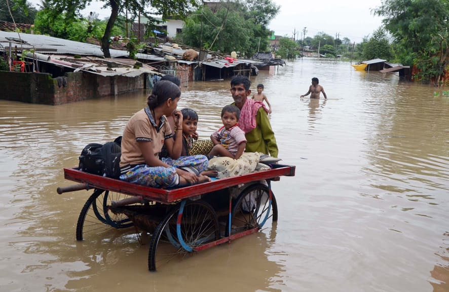 Village children sit on a cart as they are moved to safer areas after their homes were submerged in floodwaters in Hoshangabad in the central Indian state of Madhya Pradesh.