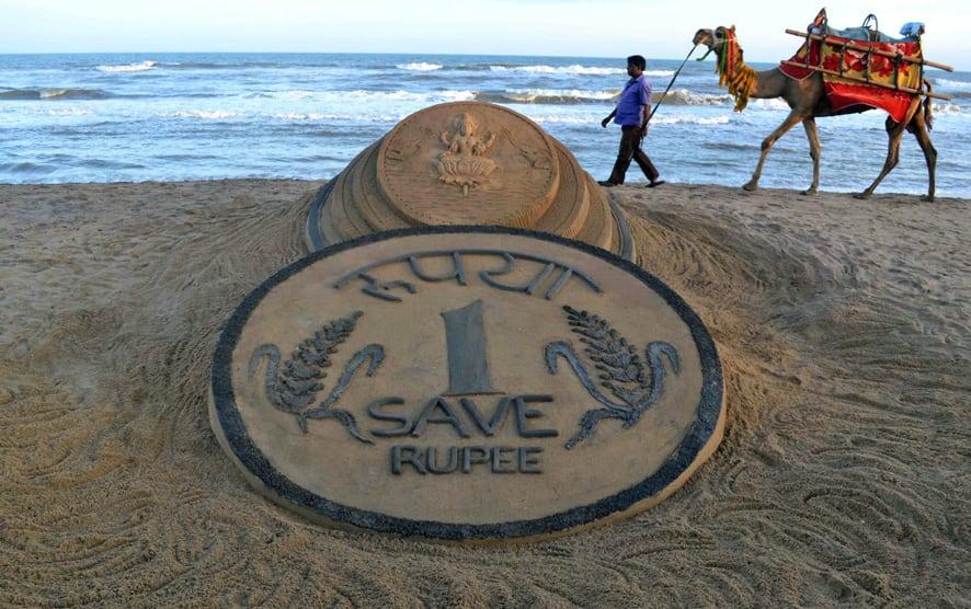 A man walks past a sand sculpture of a rupee coin on a beach in Puri.