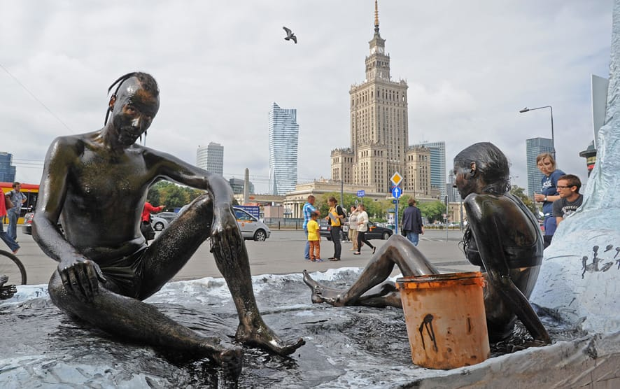 Greenpeace activists sit on a stage resembling ice, with oil spread over their bodies, protesting against oil search drilling in the Arctic Sea in Warsaw, Poland.