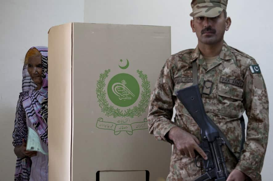 An elderly woman carries a ballot as a Pakistani army soldier stands alert during elections in Islamabad, Pakistan.