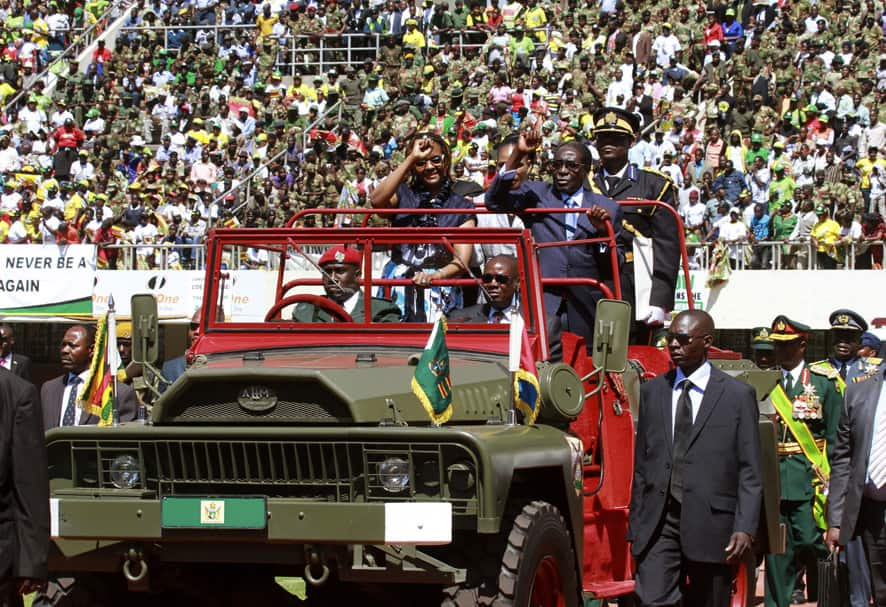 Zimbabwean President Robert Mugabe and his wife Grace greet the crowd as they arrive for his inauguration in Harare.