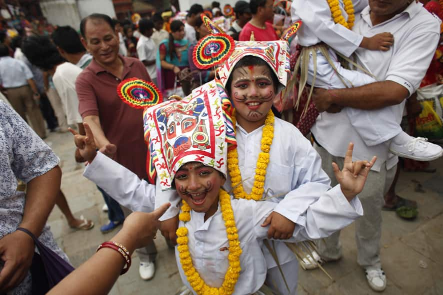 Nepalese Hindu boys in festival attire react to cameras during