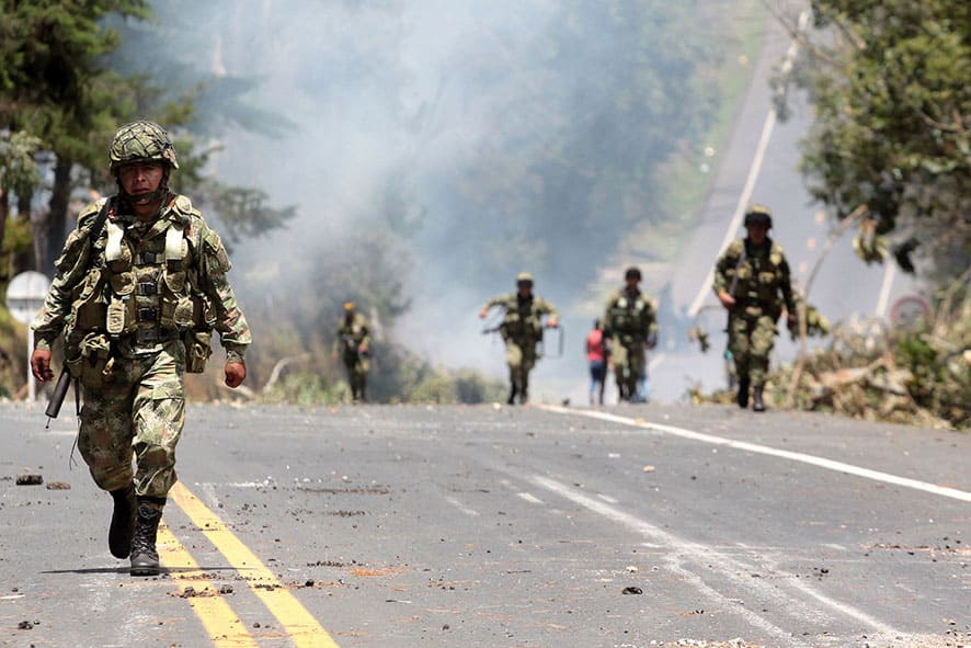 Army soldiers march along the Pan American Highway during clashes with protesters in Piendamo, southern Colombia.