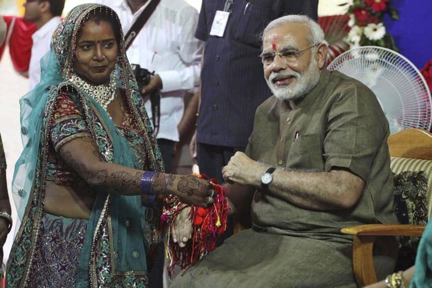 A woman ties Rakhi or sacred thread on the wrist of Gujarat chief minister Narendra Modi on Raksha Bandhan festival in Gandhinagar.