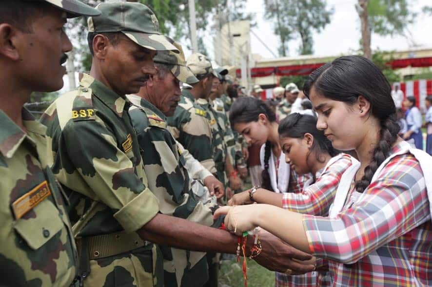 Schoolgirls tie rakhis, a sacred thread, on the wrists of Border Security Force soldiers as a symbolic gesture to mark