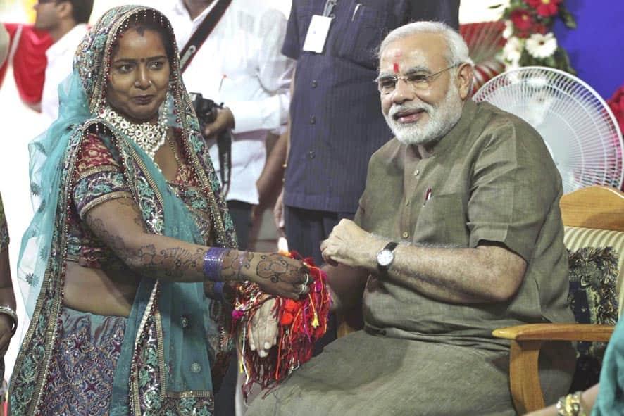 Woman ties Rakhi or sacred thread on the wrist of Gujarat chief minister Narendra Modi on Raksha Bandhan festival in Gandhinagar.
