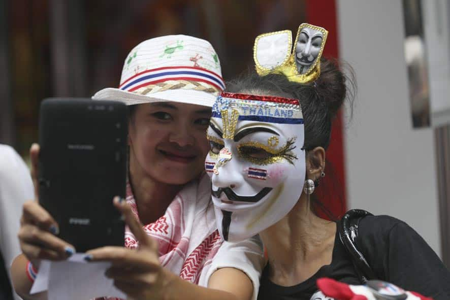 Thai demonstrators take photos of themselves during a rally against the government in Bangkok.