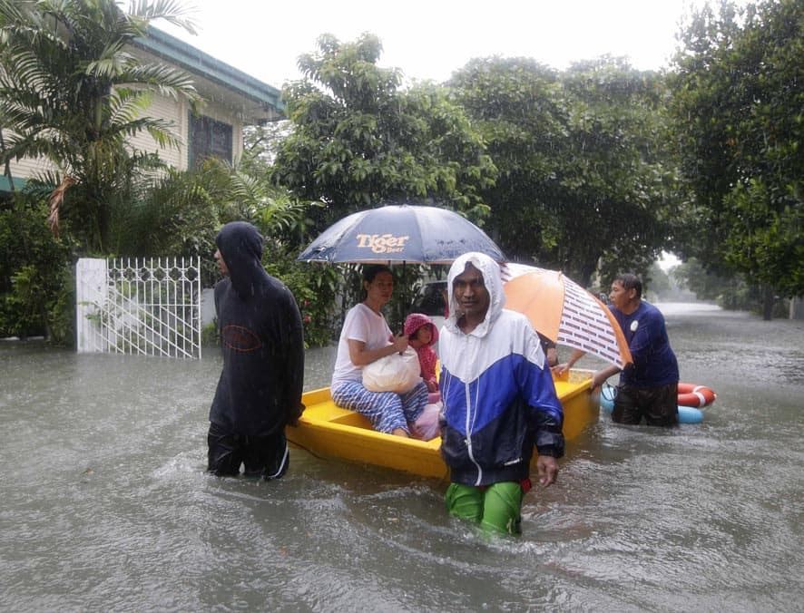 Volunteers rescue residents trapped in a flooded street at a subdivision in Makati city, east of Manila, Philippines.