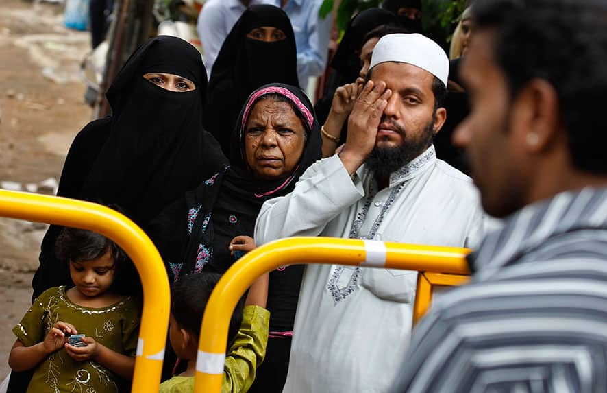 A Muslim family watches rescuers work at the site of an under construction building, which collapsed partially in Bangalore.