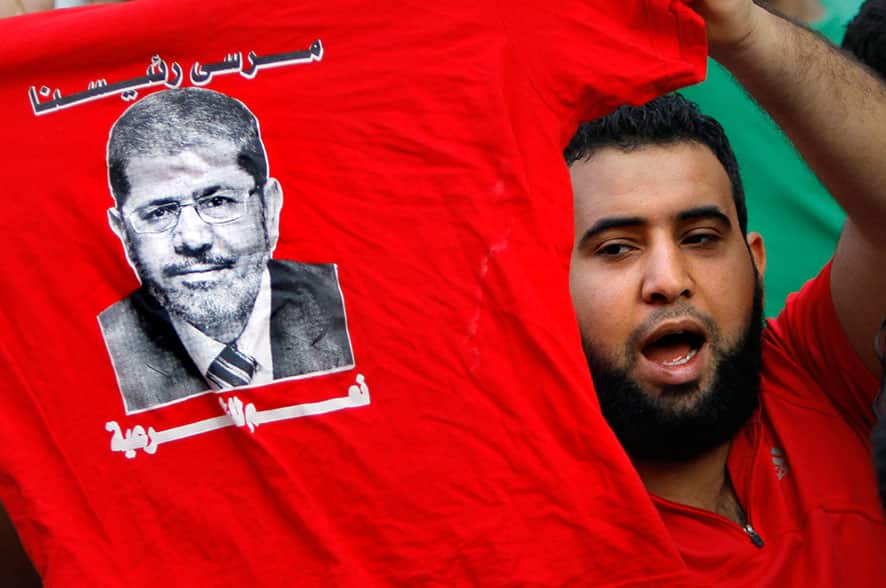 A supporter of Egypt`s ousted President Mohammed Morsi holds a T-shirt with his picture during a march in Maadi, Cairo, Egypt.