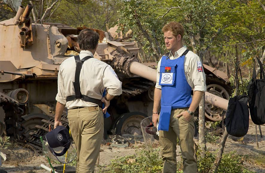 Britain`s Prince Harry, right, speaks with HALO Director Guy Willougby as they stand near a South African Olifant tank destroyed in the Battle of Cuito Cuanavale in 1988, in Angola.