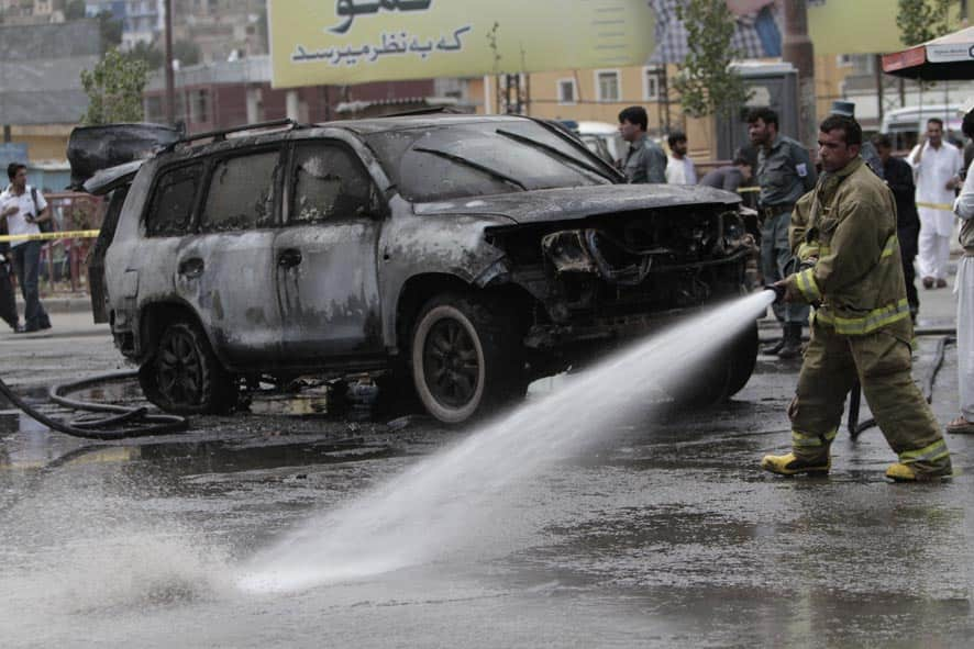 Afghan security forces investigate the scene of an explosion while firefighters spray water on the area, in Kabul, Afghanistan.