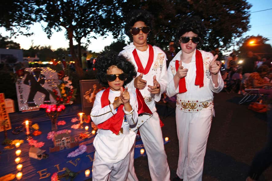 Nicholas Woodlief, 7, left, his sister Annabelle Woodlief, 11, and friend, Eli Crain, 11, right, strike an Elvis Presley pose at Graceland, Presley`s home, before the annual candlelight vigil, in Memphis, Tenn.