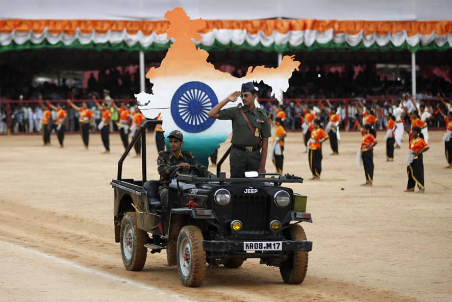 An Indian school student dressed in military attire takes the salute as he performs with others during a function to mark India`s Independence Day in Bangalore.