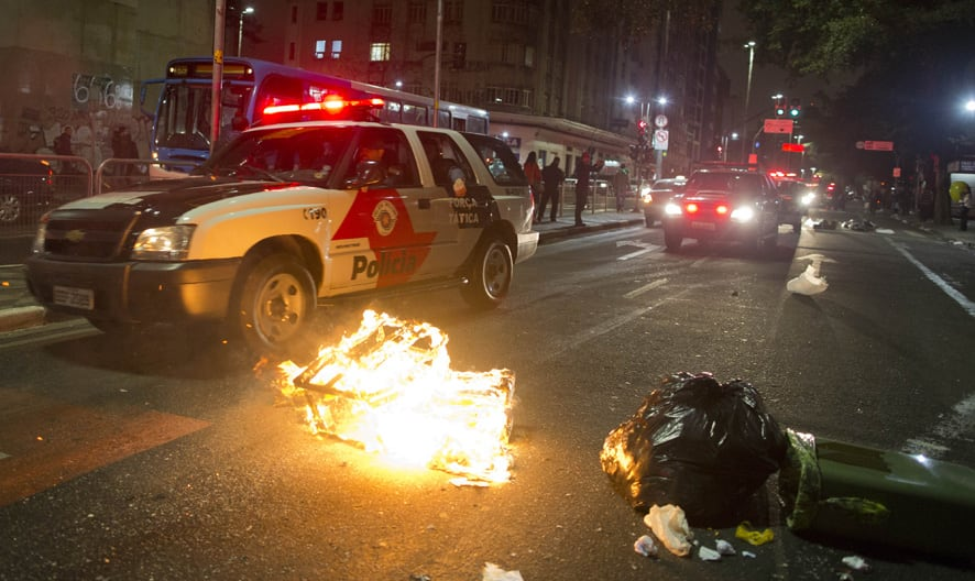 A police vehicle drives past a burning trash during a protest against Sao Paulo Governor Geraldo Alckmin in Sao Paulo, Brazil.