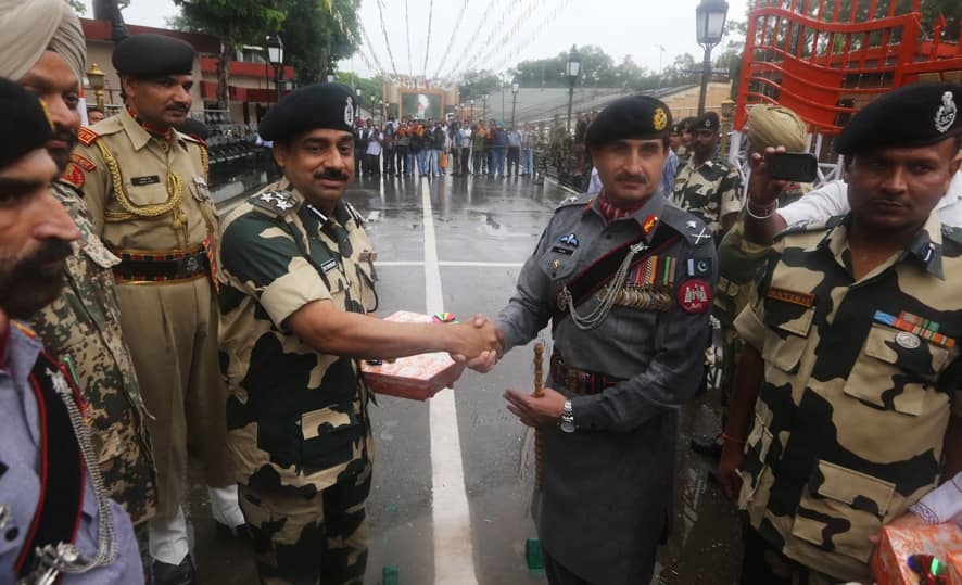 Pakistan troops, right, give sweet to their Indian counterparts on the occasion of Pakistan`s Independence Day at Wagah border in Pakistan.
