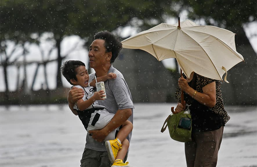 A family from Mainland China battle against strong wind near the waterfront in Hong Kong. Typhoon Utor lashed Hong Kong with wind and rain, closing down the bustling Asian financial center Wednesday before sweeping toward mainland China.