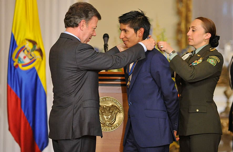 Colombia cycling rider Nairo Quintana, center, is decorated with the Grand Cross of the Order of Boyaca by Colombia`s President Juan Manuel Santos at the Presidential Palace in Bogota, Colombia.
