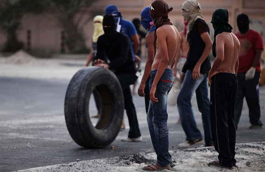A Bahraini anti-government protester rolls a tire towards burning tires on a street in the western village of Malkiya, Bahrain.