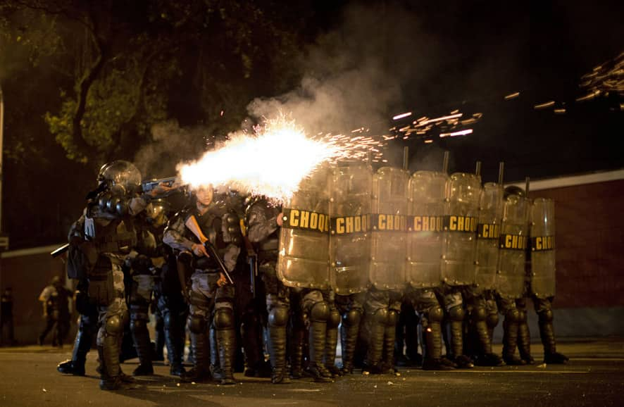 Riot police officers fire tear gas canisters during a protest against the governor of Rio de Janeiro state, Sergio Cabral, outside the Guanabara Palace in Rio de Janeiro, Brazil.