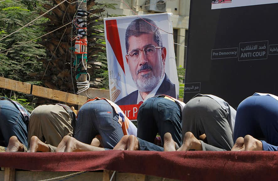 Supporters of Egypt`s ousted President Mohammed Morsi pray in front of his poster in Nahda Square, where protesters have installed their camp near Cairo University in Giza, southwestern Cairo, Egypt.