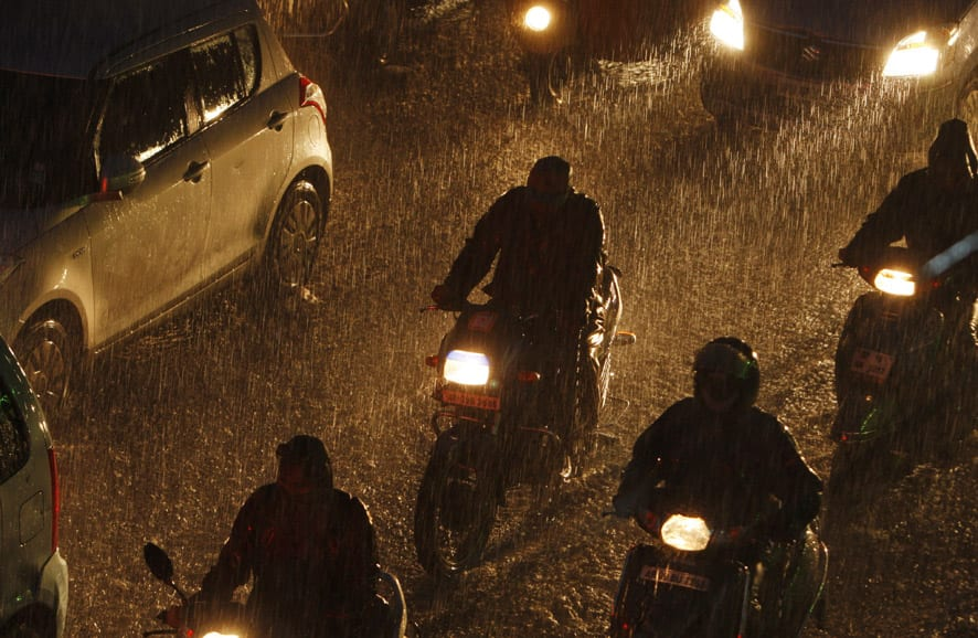 Motorists ride through a street as it rains in Hyderabad.