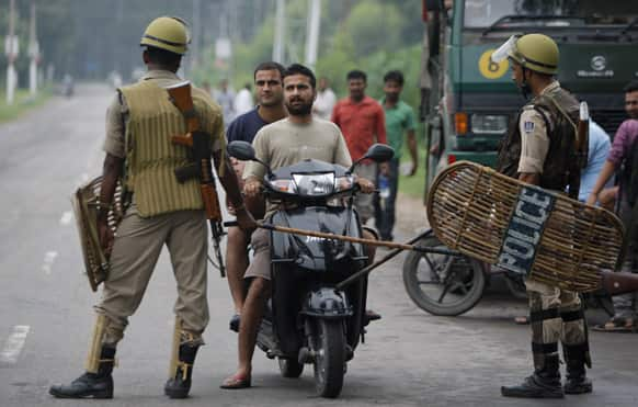Paramilitary soldiers stop commuters on a scooter during a curfew in Jammu.