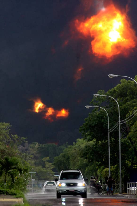 People look at smoke from a refinery fire in Puerto La Cruz, Venezuela. Lightning set fire to a storage tank at Venezuela`s Puerto La Cruz oil refinery and residents were moved out of the immediate area while local media showed images of thick black smoke rising from the facility.