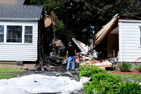 Officials inspect the debris, after a small plane, piloted by Bill Henningsgaard, crashed into two homes Friday in East Haven, Conn. Four people were killed in the incident.