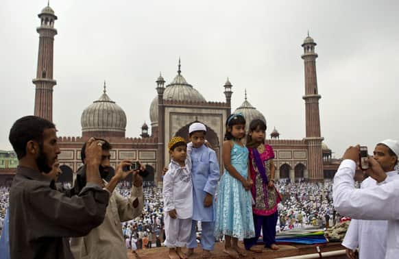 Muslims take photos after offering Eid al-Fitr prayers at Jama Masjid in New Delhi.
