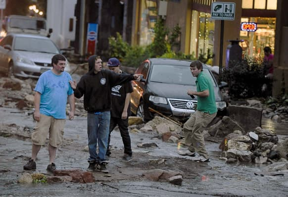 People look in disbelief as they see the damage on Park Avenue after a flash flood ripped through downtown, in Manitou, Colo.