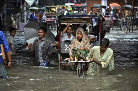 Rickshaw drivers ferry commuters past a waterlogged street after heavy rainfall in Agra.
