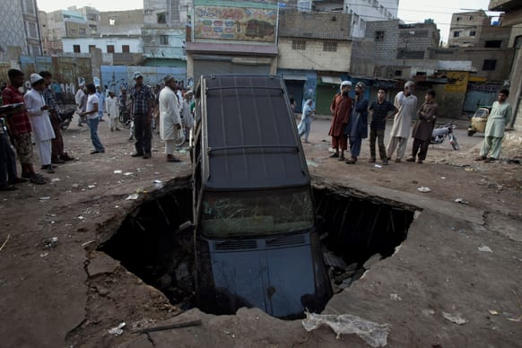Pakistani residents investigate damages caused by a bomb explosion early morning in Karachi, Pakistan.