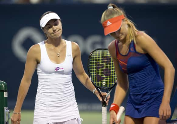 Martina Hingis of Switzerland and Daniela Hantuchova of Slovakia react during their loss to Julia Goerges, of Germany, and Barbora Zahlavova Strycova, of the Czech Republic, in a doubles match at the Rogers Cup women`s tennis tournament Thursday, Aug. 8, 2013, in Toronto.