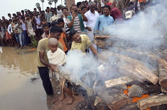 Vivek Kumar lights the pyre of his father Indian army soldier Vijay Kumar Rai, allegedly killed by Pakistani soldiers, on the banks of the Ganges River in Patna.
