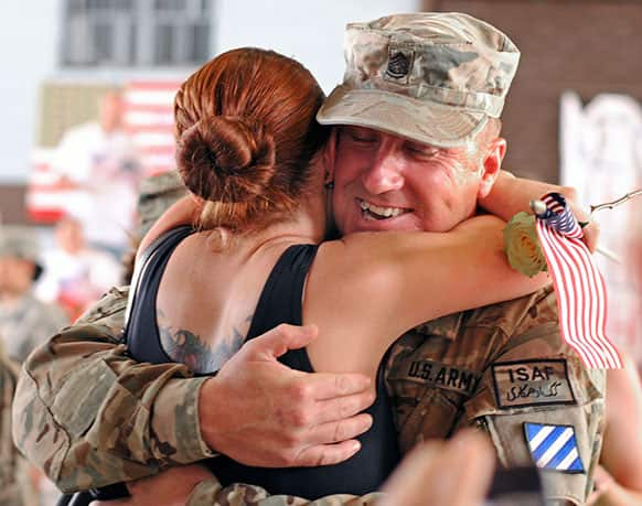 Army Sgt. 1st Class James Conway wraps his fiance Heather Woodruff at Hunter Army Airfield, Ga.