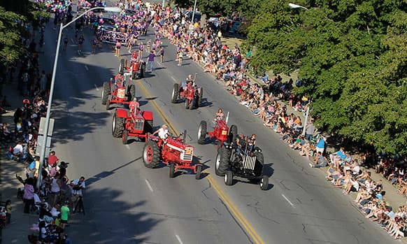 Old tractors cruse down Grand Avenue during the Iowa State Fair parade in East Village of Des Moines, Iowa.