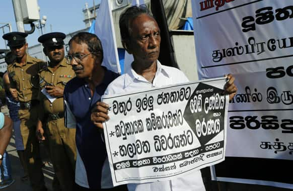 A Sri Lankan man holds a placard criticizing a recent military crackdown of a protest by villagers as police officers watch in Colombo, Sri Lanka.