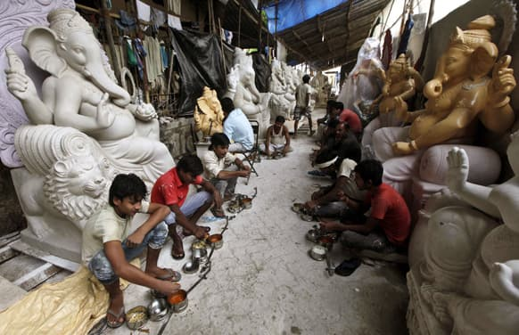 Workers eat food while taking a break from preparing idols of God Ganesh for sale for the upcoming Ganesh Chaturthi festival at a workshop in Mumbai.