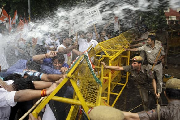 Activists of Congress party`s youth wing try to break barricades as police use water cannon to stop them during a protest against the death of five Indian army soldiers in cross-border exchanges, New Delhi.