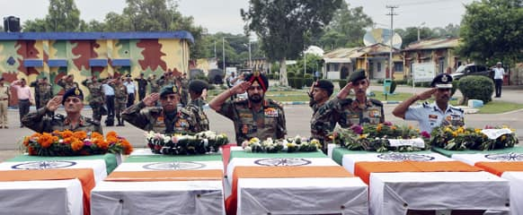 Indian army chief General Bikram Singh, center, and other army officers salute next to the coffins of Indian soldiers allegedly killed by Pakistani soldiers during a wreath laying ceremony in Jammu.
