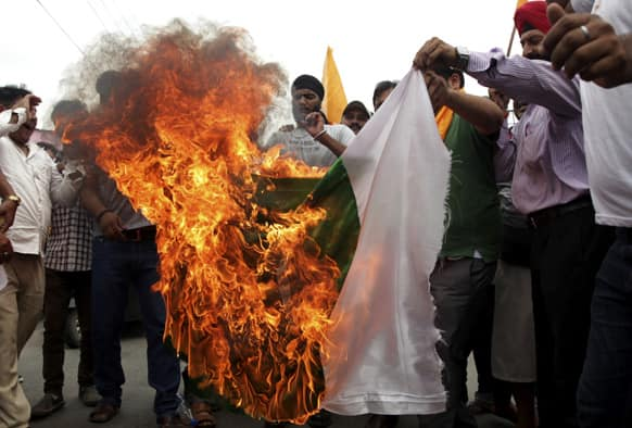 Activists of Shiv Sena burn a Pakistani flag during a protest against the death of five Indian army soldiers in cross-border exchanges, in Jammu.
