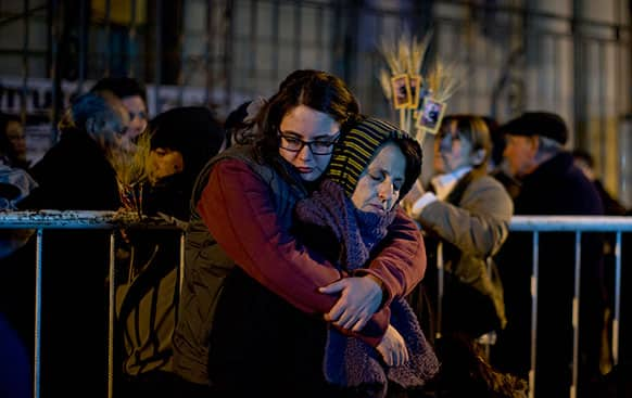 Catholic faithful embrace as they wait outside Saint Cayetano Basilica for the temple to open at midnight in Buenos Aires, Argentina.