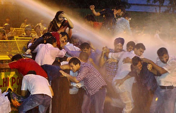 Activists of youth wing of Bharatiya Janata Party are drenched by water cannon jets by police during a protest against the death of five Indian army soldiers in cross-border exchanges, in New Delhi.