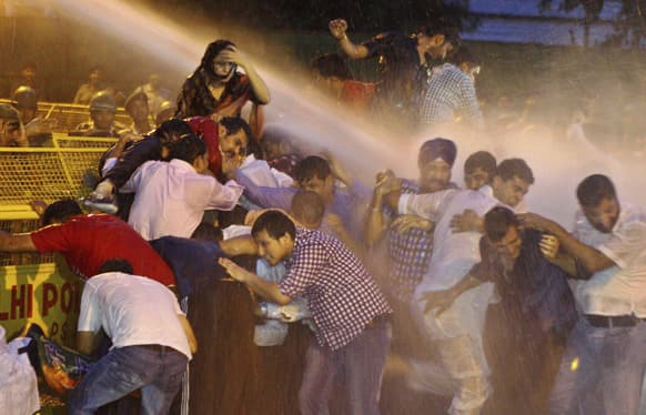 Activists of youth wing of Bharatiya Janata Party (BJP) are drenched by water cannon jets by police during a protest against the death of five Indian army soldiers in cross-border exchanges, in New Delhi.