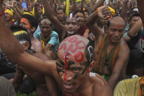 """All Bodo Students Union activists shout slogans as they demand the creation of new state called """"Bodoland"""" during a mass rally on a national highway in Barama, in lower Assam."""